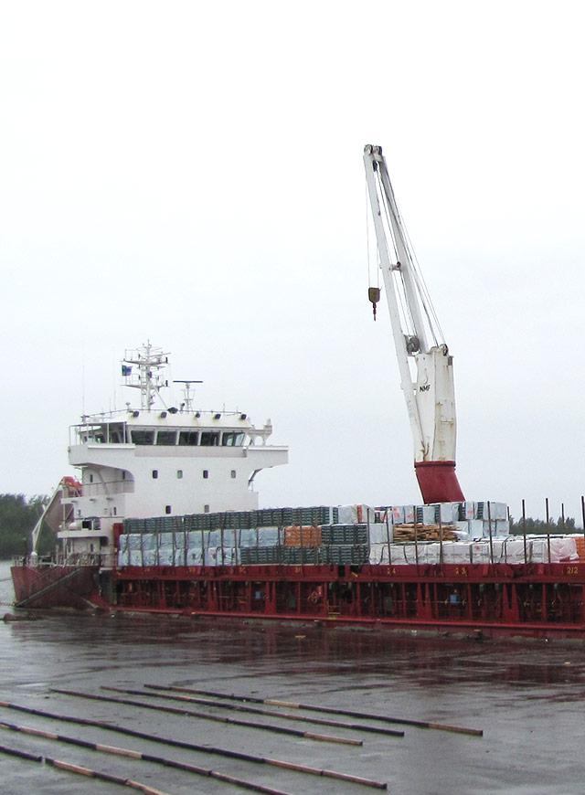 目的地向けて製材品を積んだ輸送船が出港する場面